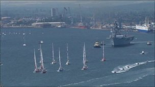 The yachts leave Southampton with HMS Illustrious in the background