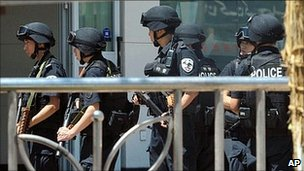Armed members of Chinese Special Police Corps stand guard near the site of Sunday's attack in Kashgar