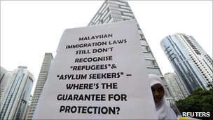 A demonstrator holds a placard outside the venue of the signing ceremony between Malaysia and Australia to swap refugees in Kuala Lumpur on 25 July 2011