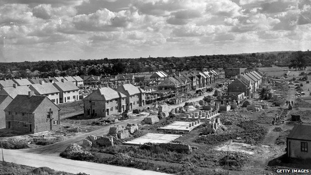 Clouds gather over the long lines of identical houses on a council estate under construction. It is being built by various small building firms each constructing a few houses., 1947