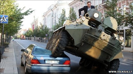 Mayor Arturas Zuokas in an armoured vehicle which is crushing a car in central Vilnius