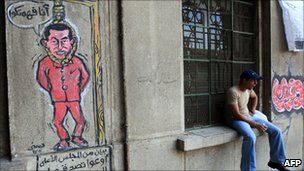 An Egyptian man sits close to graffiti depicting former president Hosni Mubarak hanging at the gallows - 27 July 2011