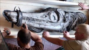 Museum staff unload the fossil which is on load from the Natural History Museum in London.