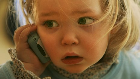 A toddler talking on a mobile phone