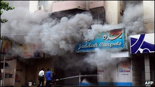 Fire fighters work to extinguish a fire in a shop torched during a fresh wave of violence in Karachi