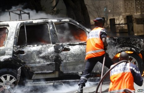 Rescue workers try to extinguish a car set on fire in Dakar (June)