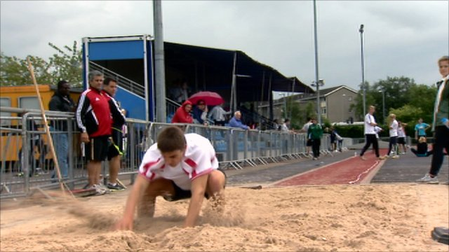 Long jump competitor lands in the sand