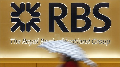 Woman with umbrella walks past RBS