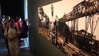 Visitors next to a work by Sammy Baloji. Photo: Manuel Toledo, BBC