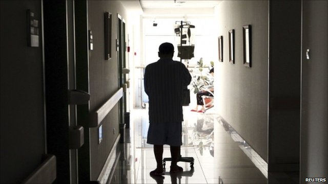 A cancer patient pushes his drip stand as he walks down the hallway of a hospital