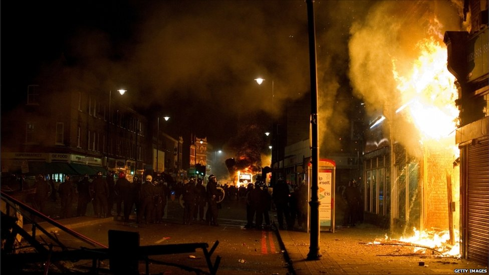 A shop and double decker bus burn as riot police try to contain a group of people in Tottenham