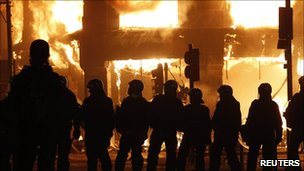 Police stand in front of a burning building