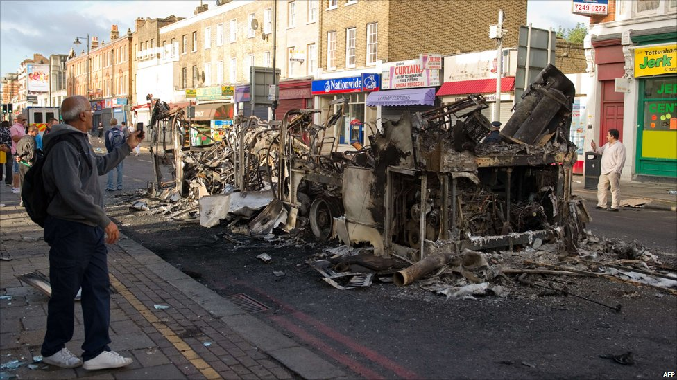 A passer-by takes a photo of the remains of a double decker bus.