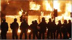 Riot police in front of burning building