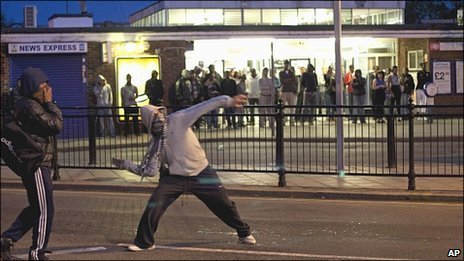 Man throws a missile during rioting in Enfield