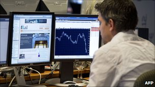 Trader on the Amsterdam stock exchange watches market movement on 8 August 2011