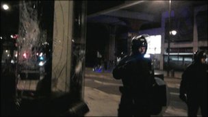 Riot police next to a smashed shop window. Copyright: Emma Reynolds and Ailsa Leslie.