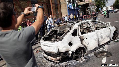 Man taking digital photo of burned out car