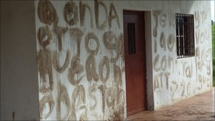 A threat is written in blood on the wall of a farm building