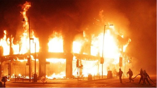 Firefighters work to put out a blaze at a building in Tottenham, north London, set alight during Saturday's riots