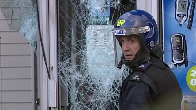 police stand outside a pharmacy in Peckham where looters vandalised the shop