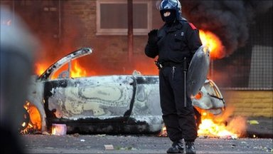 A police officer stands in front of a burning car in Hackney