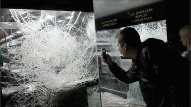 People take photos of damage caused by looters in a pawn shop on Clapham High Street