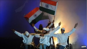 Artists in wheelchairs hold Indian flags during a performance in Bangalore on 28 May 2010
