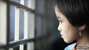 "Burmese refugee Mang Thai Par, 7, looks out of a window at her family""s flat which they share with three other relatives in Kuala Lumpur June 24, 2011"