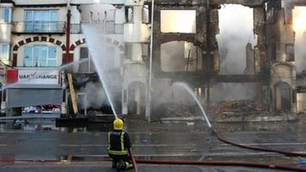 A firefighter douses a burnt out building in Croydon, south London, following the third night of riots