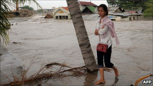 Cambodian woman walking from her house that flooded by water and sand at a village on Boeng Kak lake November 8, 2010