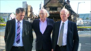 Maurice Reeves with his two sons i  front of his burnt out shop