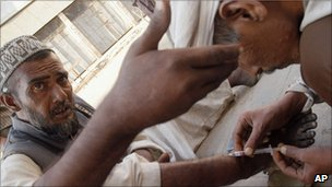 Pakistani drug addicts using syringes in Karachi
