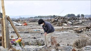 A woman who lost her family in the March 11 earthquake and tsunami prays in the city of Minamisoma in Fukushima prefecture on May 2, 2011