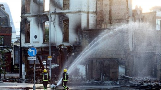 Firemen hose water onto a building that was burnt during riots in Croydon, south London