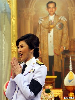 Yingluck Shinawatra gestures after receiving the royal command appointing her as prime minister in front of a portrait of the Thai King