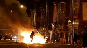A rioter walks through a burning barricade in Liverpool, where about 200 rioters in the Toxteth area chucked missiles and caused damage