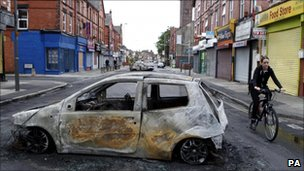 A woman cycles past a burnt out car on Lawrence road in Wavertree