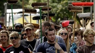 People hold brooms in Clapham, London