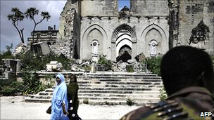 Women walking past ruined building in Mogadishu