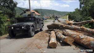 K-For troops pass a blockade in the village of Zupce near the border between Kosovo and Serbia.