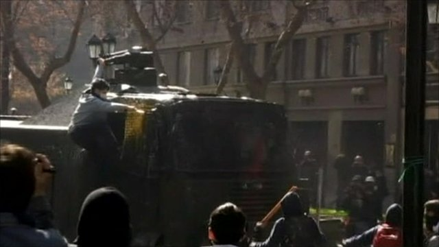 Protester climbing on tank fitted with water cannon