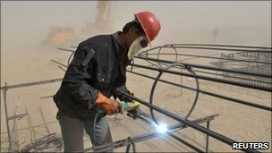 A labourer welds steel bars