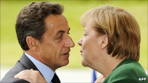 French President Nicholas Sarkozy kisses his German counterpart Angela Merkel in greeting on 20 July 2011