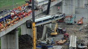 Workers clear wreckage of mangled carriages after a Chinese high-speed train derailed, July 24, 2011
