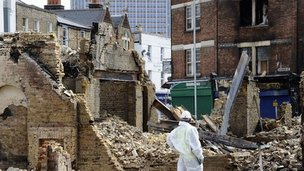 A worker stands by the remains of a furniture shop that was burnt to the ground in Croydon, south London