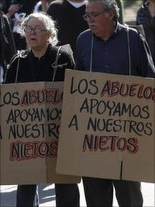 "A man and a woman demonstrate in support of Chile's students holding signs that read in Spanish ""Grandparents support their grandchildren"" in Santiago, Tuesday, 9 August 2011"