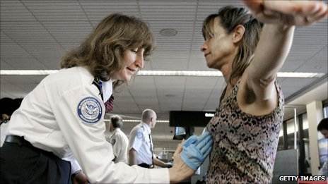 A Transportation Security Administration agent performs a pat-down on a passenger at Phoenix Sky Harbor International Airport