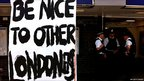 A sign urging Londoners to be nice to each other is pictured near an Underground station in north London