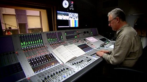 Audio engineer behind a soundboard